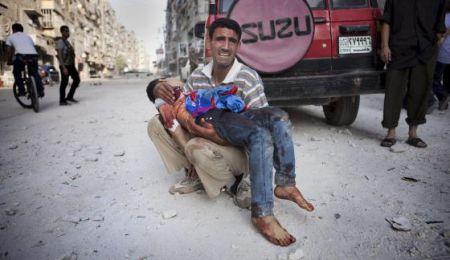 padre sujetando a su hijo muerto en Alepo (Siria)